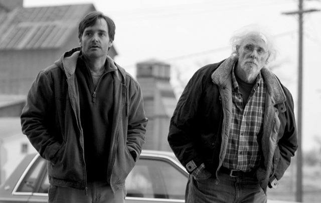 Will Forte and Bruce Dern, wearing heavy jackets and standing in a small town street, looking off-camera
