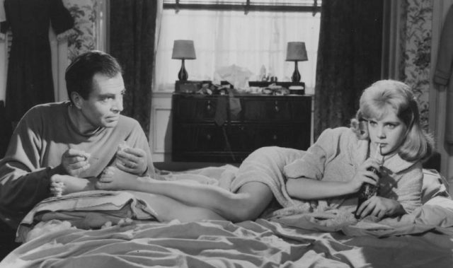 A woman lays on her side on a bed, with a man sitting at the foot of the bed looking at her