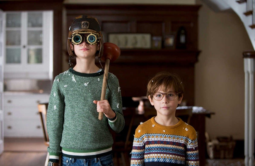 Two children stand facing a camera, with one holding a plunger over his shoulder and wearing goggles