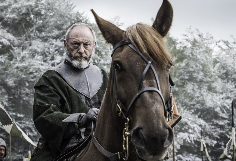 Davos riding a horse, looking sternly off into the distance