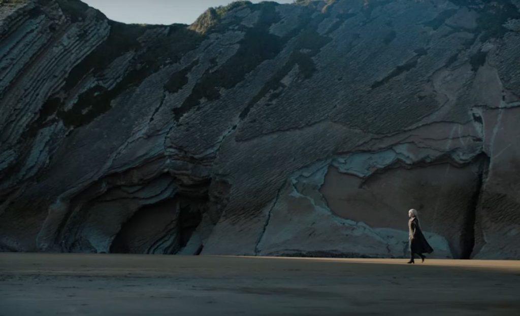 Daenerys Targaryen walking on a beach, with a tall mountainous ridge behind her