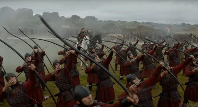 Jaime Lannister sitting on a horse behind a group of archers, who are all aiming their bows upwards.