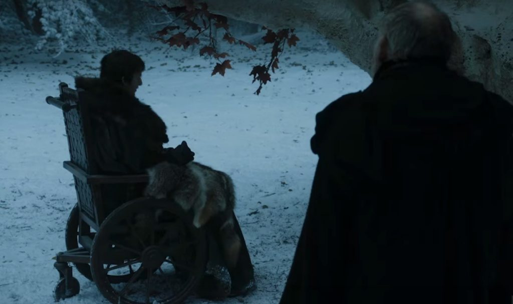 Bran, sitting in a wheelchair while an old man stands with his back to the camera next to him