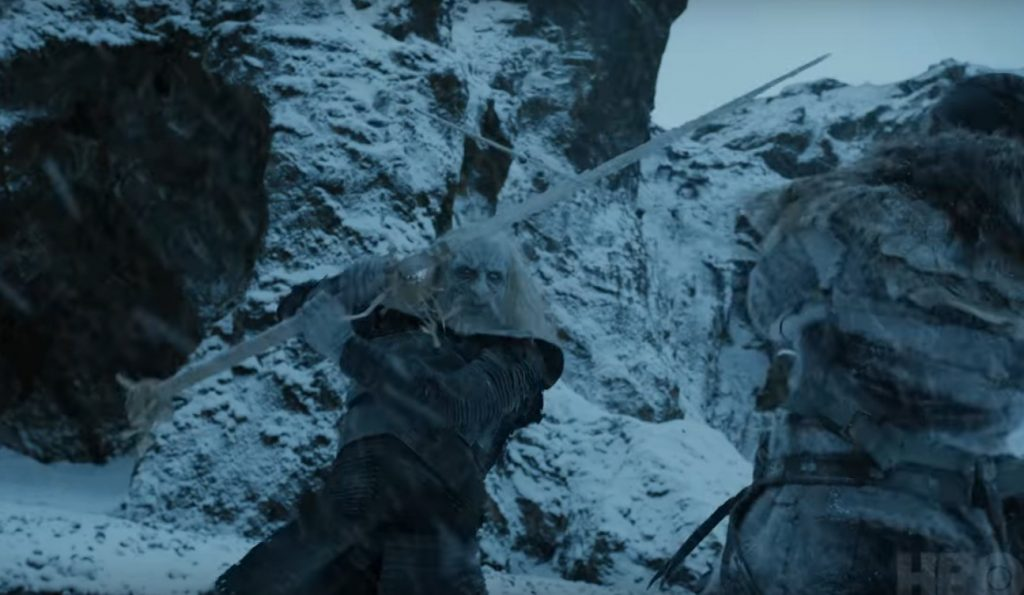 A White Walker swings a sword at a man crouched low to the ground, as the two fight in the snow in front of a ridge