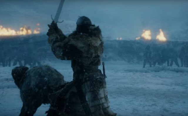 Jon Snow holding his sword over his head, as he brings it down on a man crouched on the ground in the snow