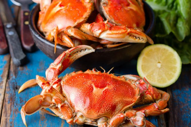 Crabs and lemon on a wooden table.