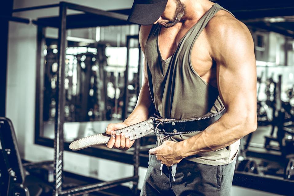 Adult bodybuilder wearing leather gym protection belt.