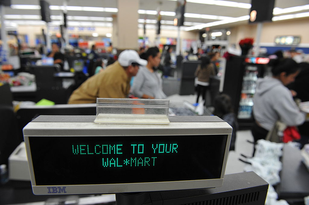Shoppers wait in line to pay