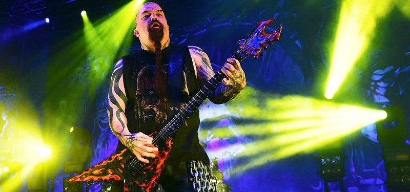 Slayer is playing on stage with bright lights.