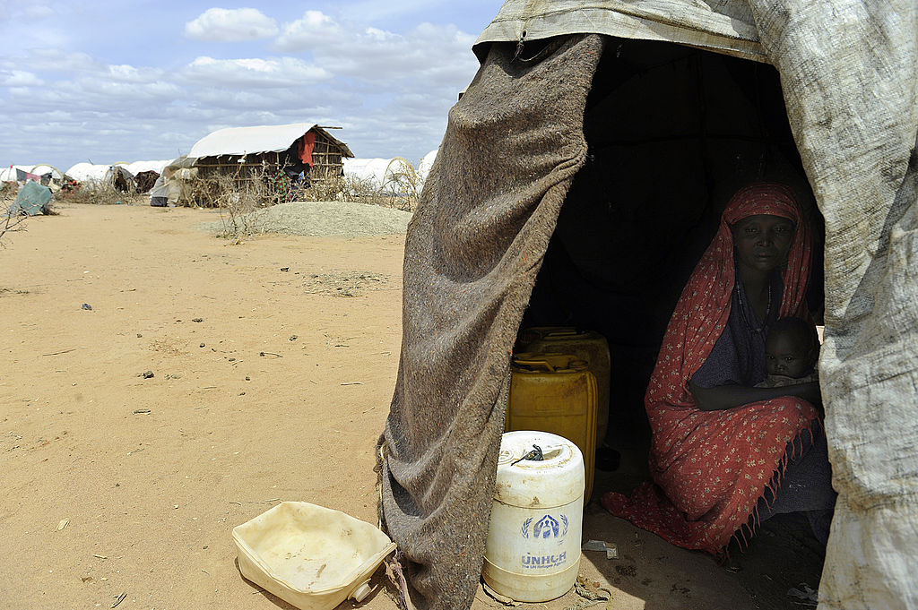 A displaced Somali mother and her children take cover from the hot sun in a makeshift shelter