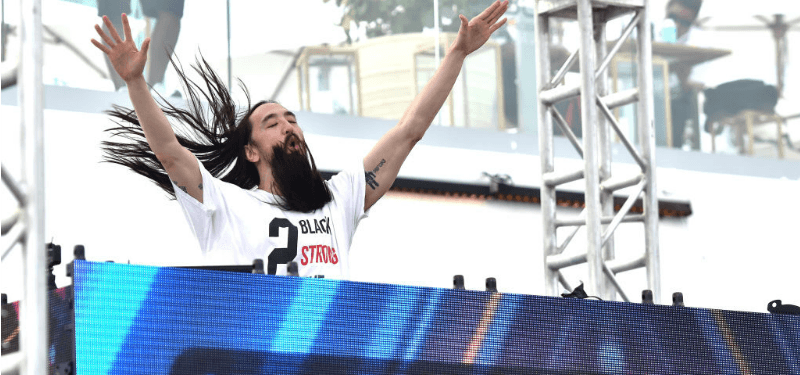 Steve Aoki has his hands in the air behind a DJ booth.