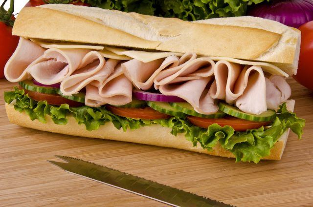 Sub sandwich on a cutting board. Tomatoes, onion and lettuce background.