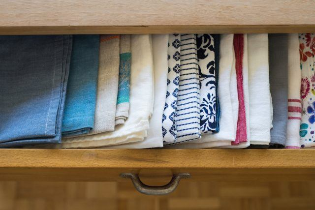 Tea towels arranged in a drawer of dining table in a way easy to find