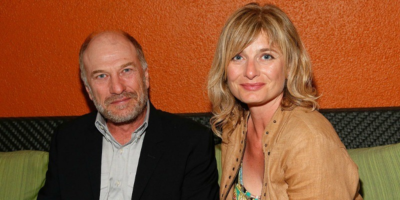 Ted Levine and his wife, Kim Phillips are sitting next to each other smiling.