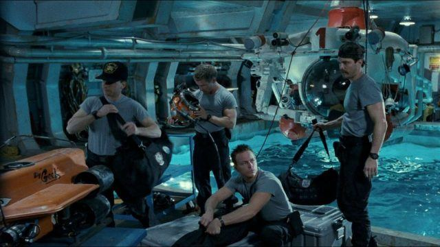 People gather in an antechamber, next to a submersible, gathering their equipment for their mission