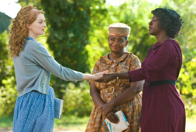 Viola Davis and Emma Stone, holding both hands together, while Octavia Spencer smiles in the background