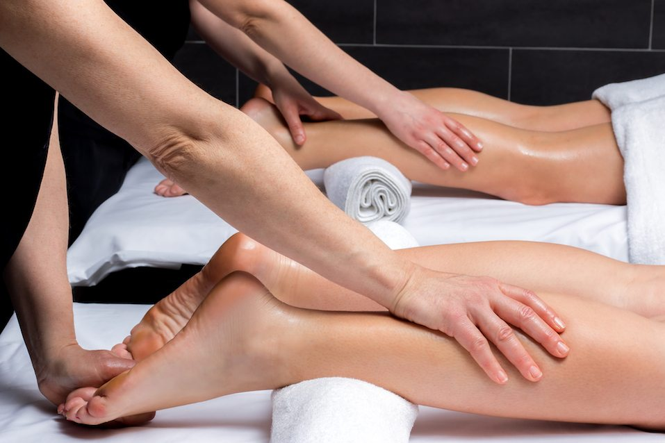 Two physiotherapists applying pressure on couples legs.