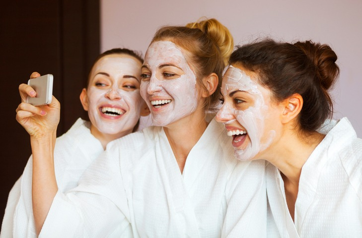 Three young happy women with face masks at spa resort.