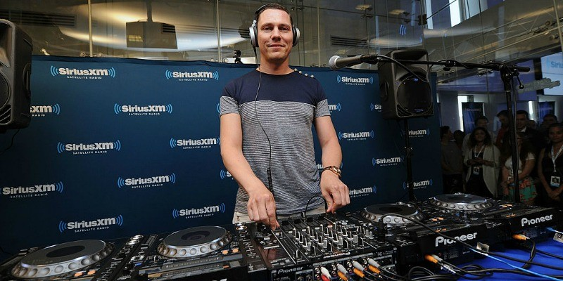 Tiesto is work on a sound board and smiling at the camera.