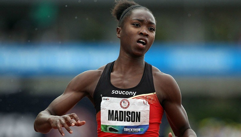 "Tianna Madison is wearing a tank top that has a sign reading ""Madison."""