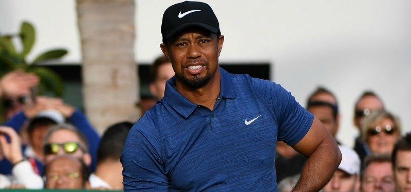 Tiger Woods is wearing a blue shirt and hat as he is on a golf course.