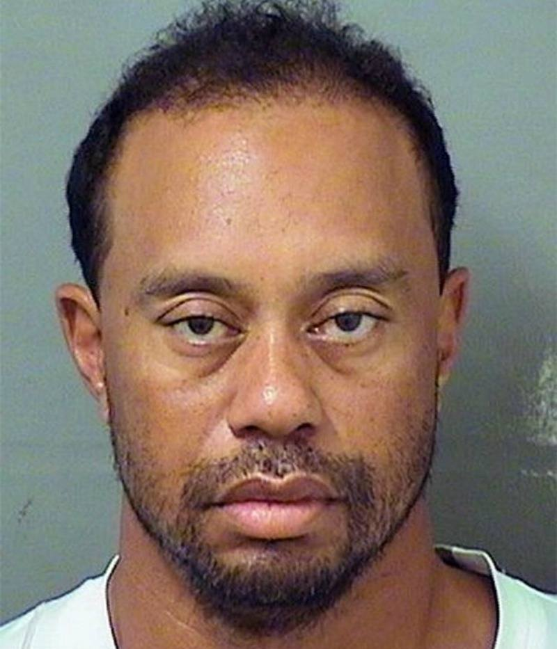 Tiger Woods is wearing a white shirt and looks disheveled.