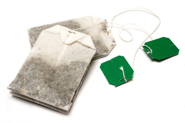 Two tea bags on a white surface.