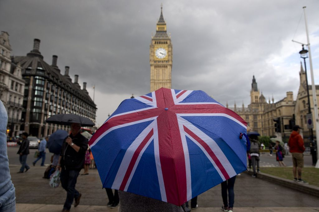 A pedestrian shelters from the rain beneath a Union Jack-themed umbrella.