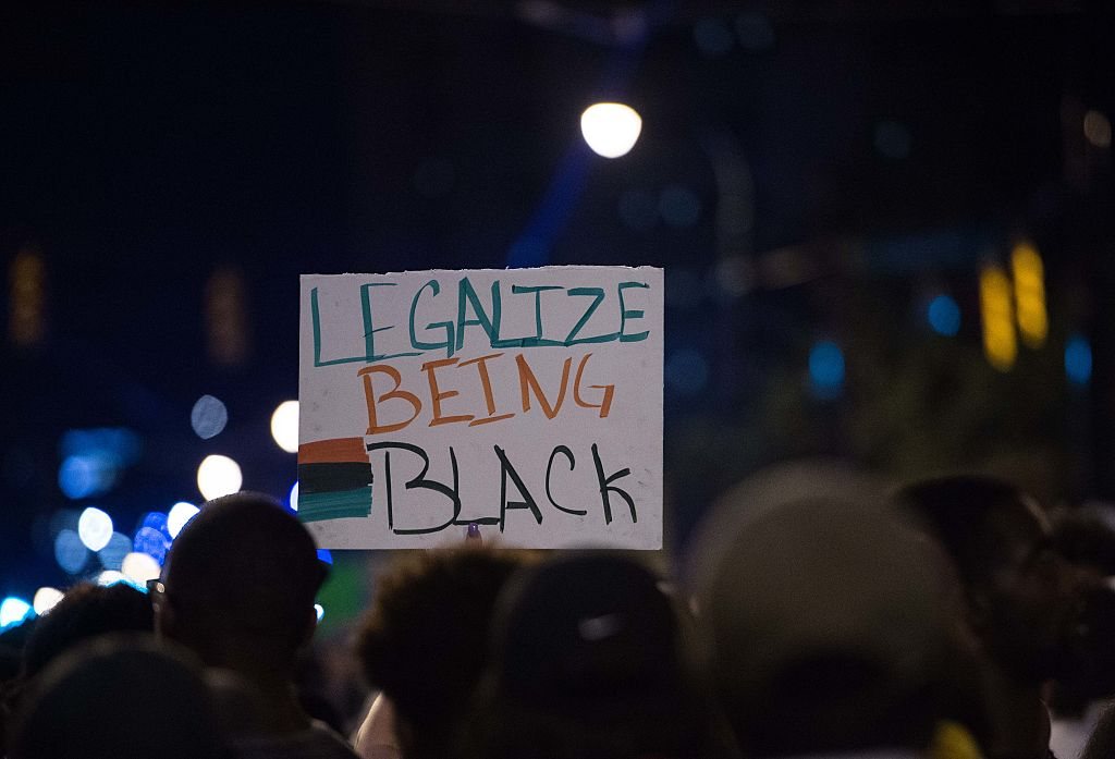 A protester holds a sign in front the Charlotte Mecklenburg Police Department
