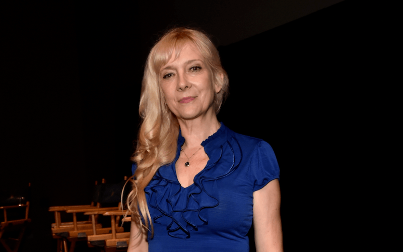 Glenne Headly stands in front of a row of chairs