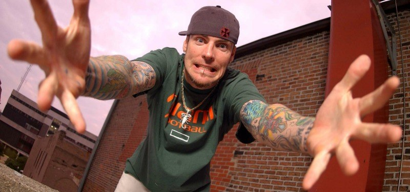 Vanilla Ice has his arms stretched out towards the camera.