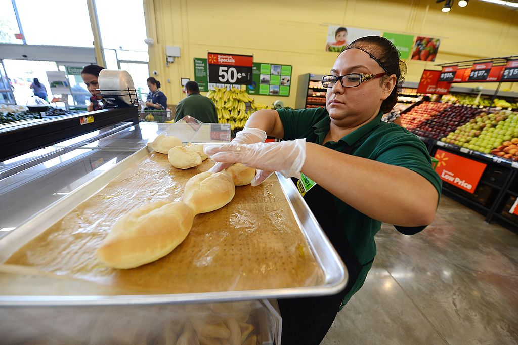 A Walmart employee takes bread off a pan.