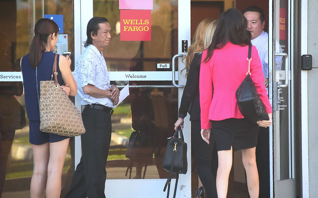 Customers await entry at a branch of Wells Fargo