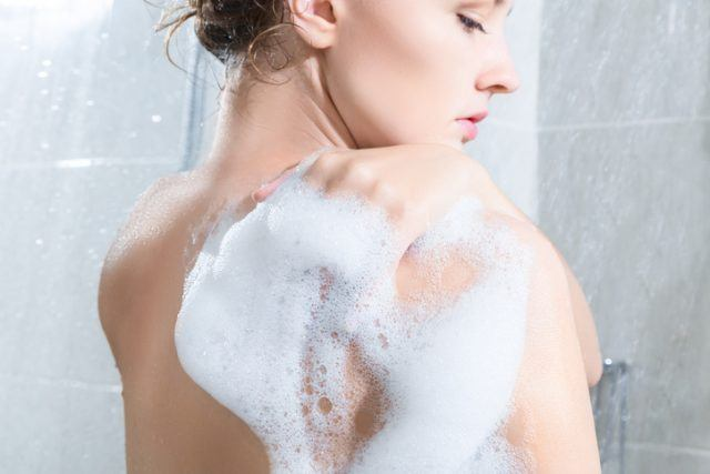 Young woman washing body in a shower in the morning light