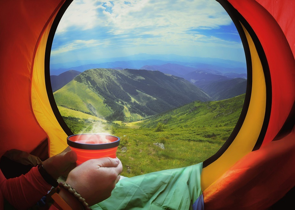 Woman lying in a tent with coffee