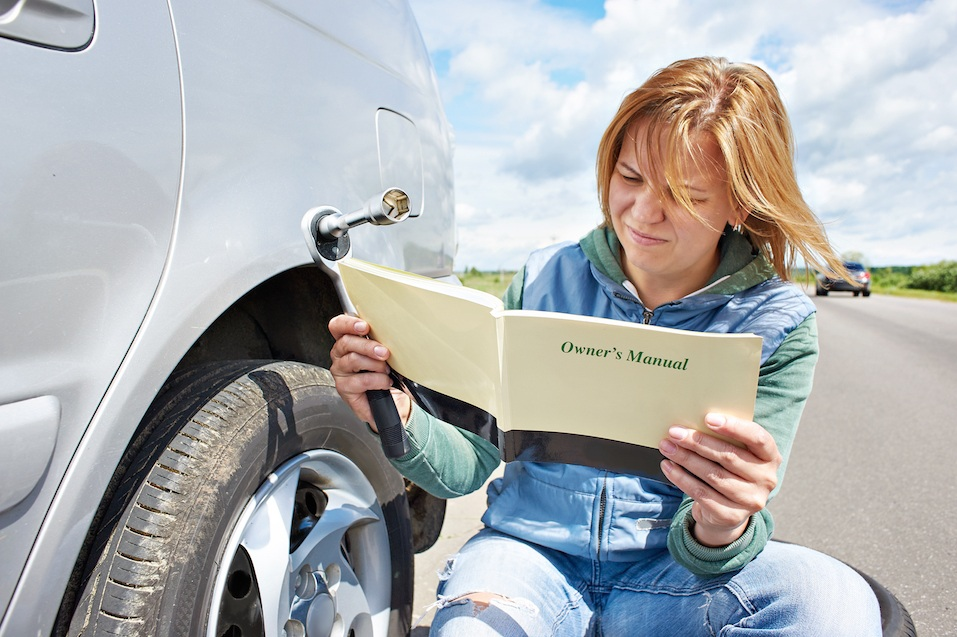 Woman reading owner's manual of her car