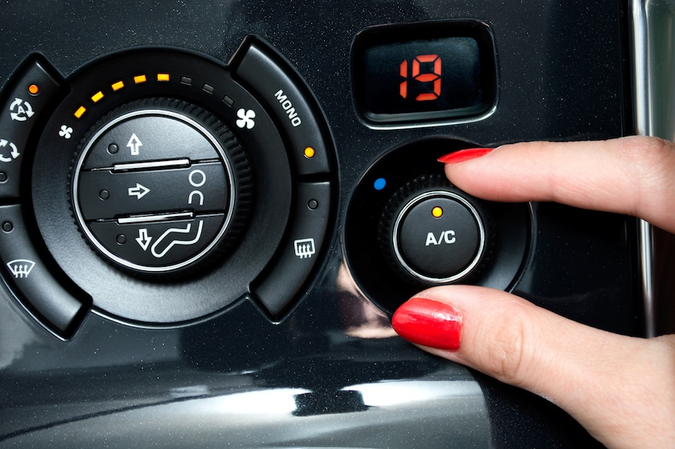 Woman turns on air conditioning in a car