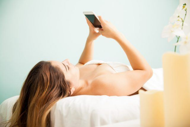 Attractive young woman using a smartphone and texting while laying on a massage bed at a spa