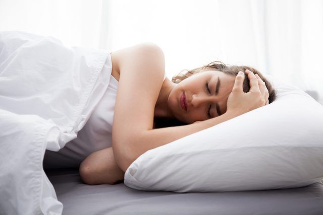 A woman sleeps on a bed with white covers and pillows.