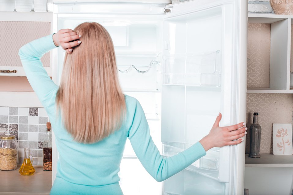 woman standing near open empty fridge