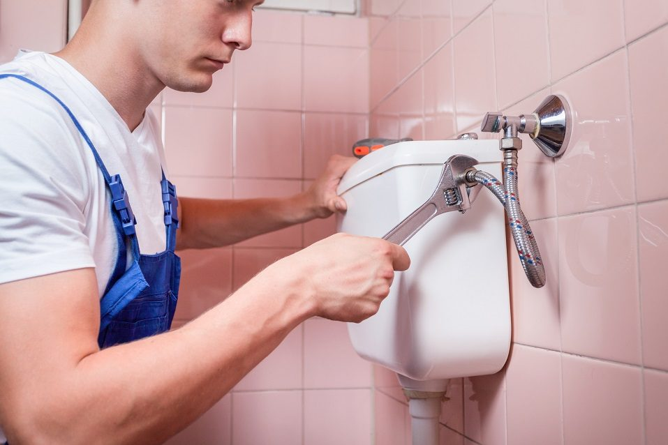 Plumber repairing a toilet pipe