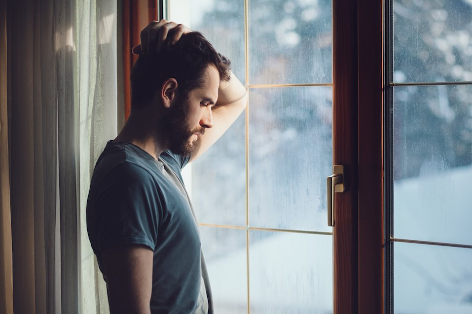 Young sad man sitting by the window