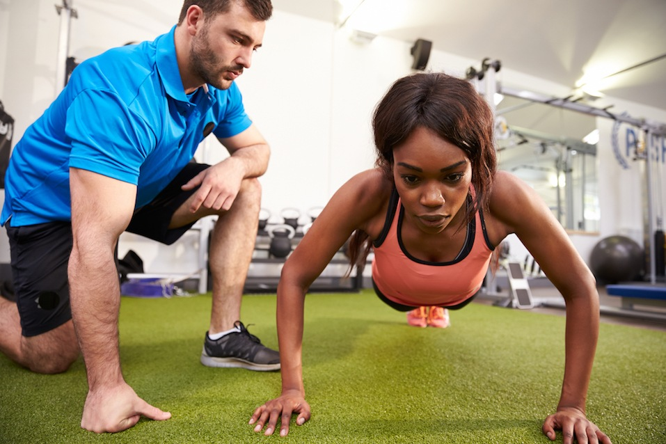 Young woman doing push ups under supervision of a trainer
