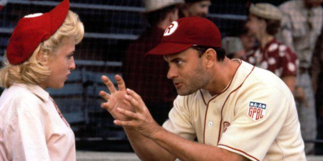 Tom Hanks in a baseball uniform, hunched over with his hands extended out toward Madonna, also in a baseball uniform