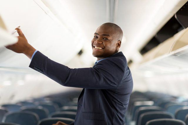 cheerful african american businessman opening overhead locker on airplane
