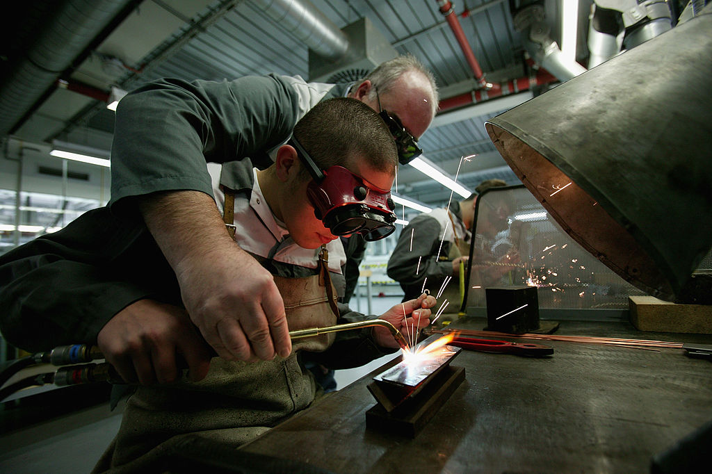 A foreman instructs a trainee in welding at training center offering apprenticeships