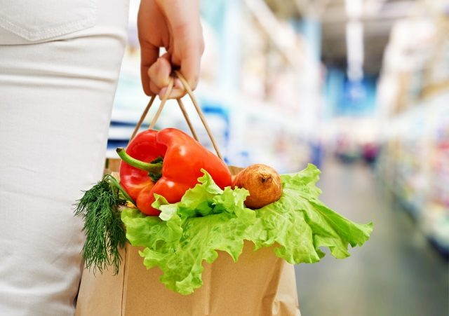 Woman holding a bag of vegetables at the grocery store