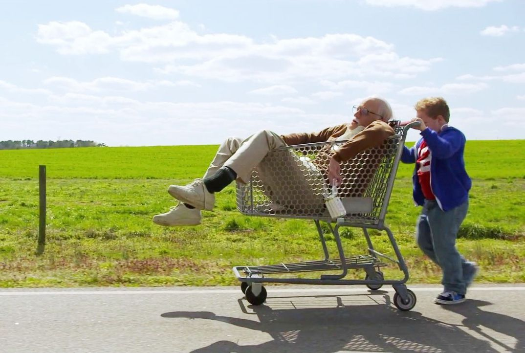"""Johnny Knoxville in """"Bad Grandpa"""" being pushed in a shopping cart"""