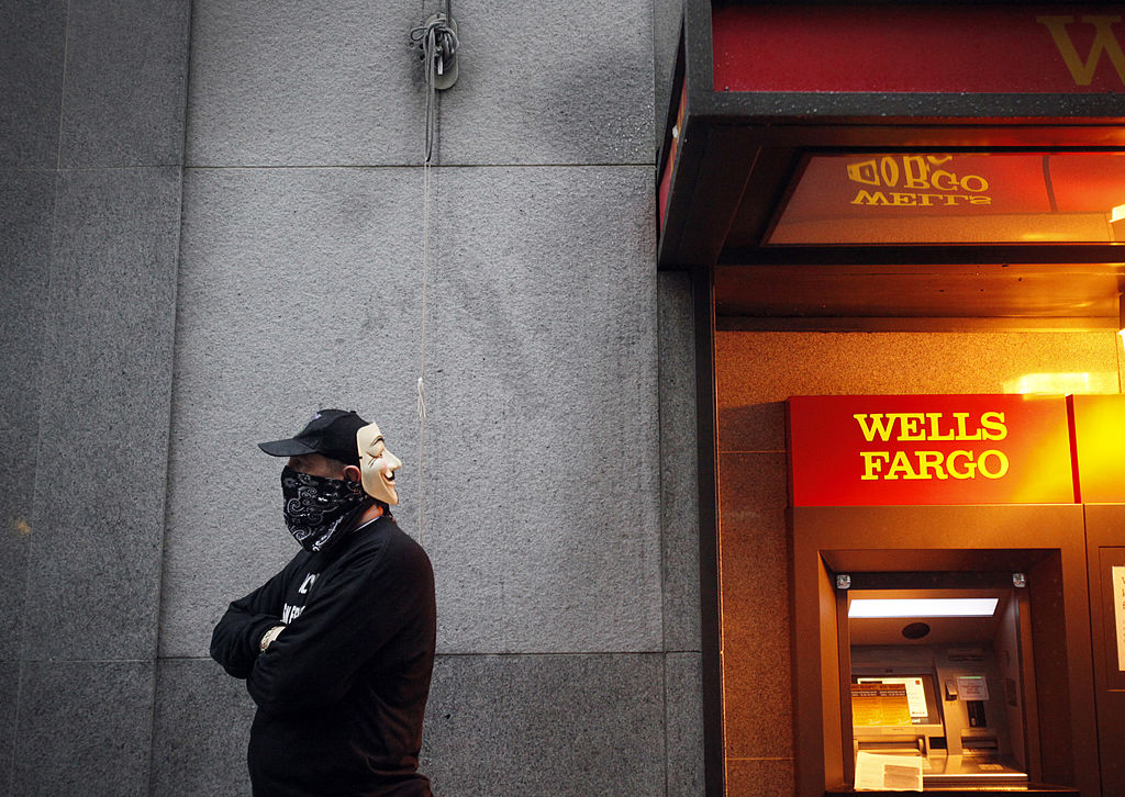 "An ""Occupy Wall Street West"" protester next to Wells Fargo ATM"