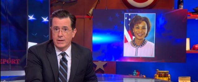 Stephen Colbert sits next to a screen that's displaying a photo of Rep. Barbara Lee on 'The Colbert Report.'